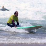 Knees ride, controlling the surfboard. R Star surf school Carrapateira at Amado beach, Algarve