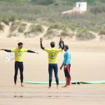 warm up R Star surf school beginners getting ready for they first surf lessons at Amado beach, Carrapateira, Algarve