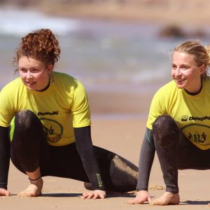 yellow rash vest warming up at amado beach, one of many great surf lessons of R Star Surf School of Carrapateira, Algarve, Portugal.
